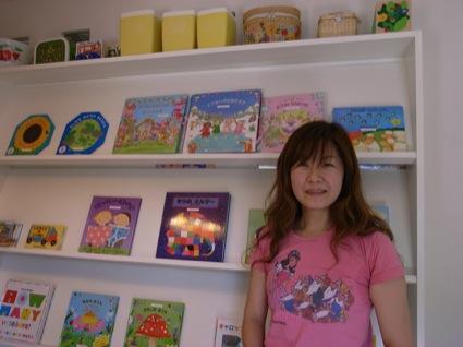 冨岡ゆきさん。自宅ショップ「lalaru」にて。後ろの本棚には、世界の名作の仕掛け絵本がたくさん