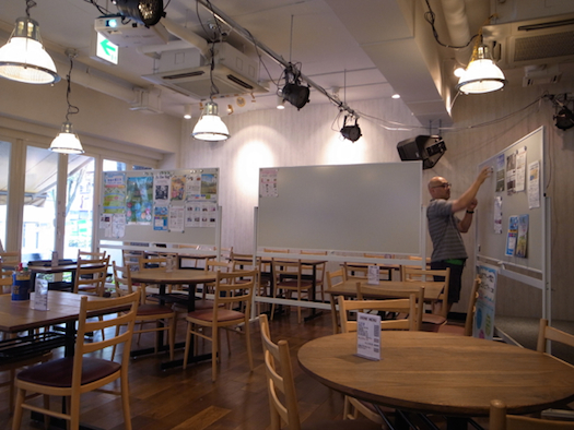 店内の様子(グランドオープン前)。以前のカフェが内装やテーブルセットを残して退去したのを、ほとんどそのまま利用した。案内チラシが貼ってあるのはホワイトボード。空間を仕切ったり、打ち合わせに使ったりと重宝しているとのこと