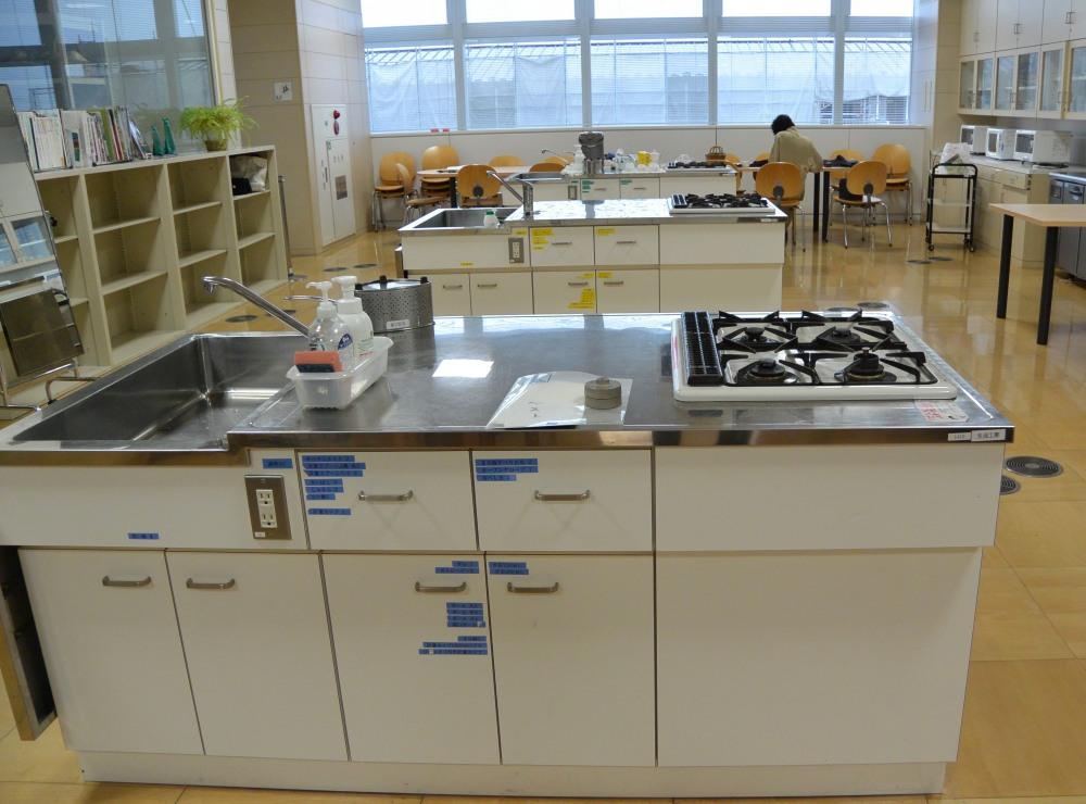 使いやすい大きめの流しと4個口コンロのついた調理台。天井には大きな換気扇がついている