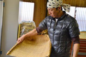 穀箕(こくみ)を持つ9代目の川口恭さん。夏は農家として、無農薬の野菜づくりに精を出す