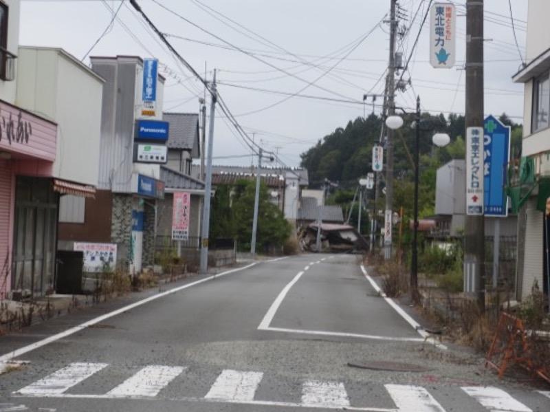 井上さんが一時帰宅の皆さんに同行した折に撮影した、双葉町の駅前の通り。崩れた家がそのまま残っている(写真提供:井上仁さん)