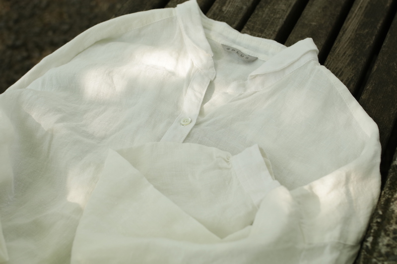 夏のシャツワンピースのホワイト。羽織るとゆとりのある大きさに上品な小さな襟がかわいらしさをプラス