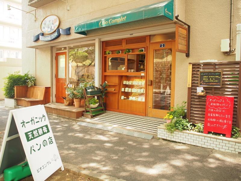 桜並木の木漏れ日の中で目を引く看板と、木とグリーンの相性がかわいらしいお店の外観