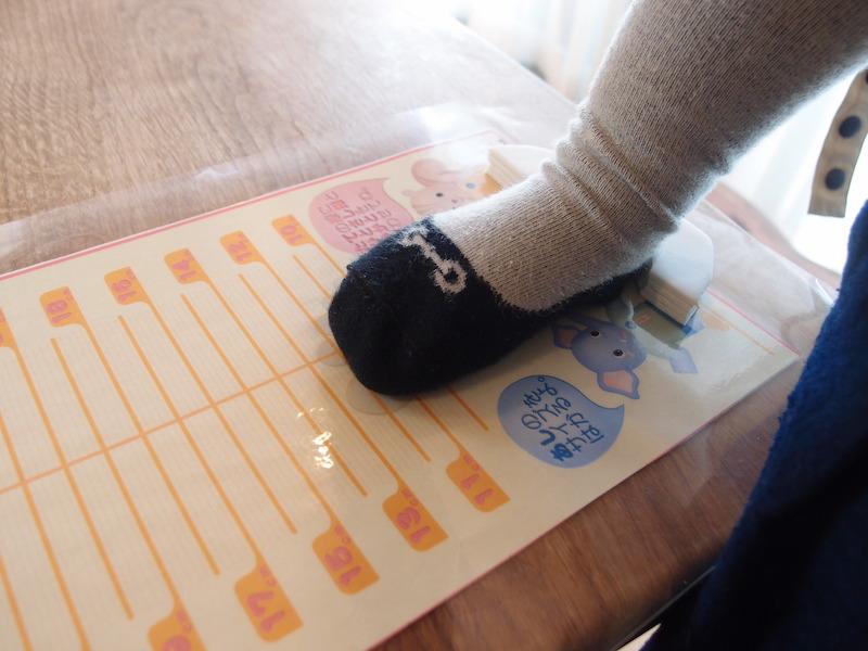 寝ているわが子の足を計測シートに置いてみる。実際は子どもを立たせてしっかり足で地面を踏みしめた状態でサイズを測ることが大切