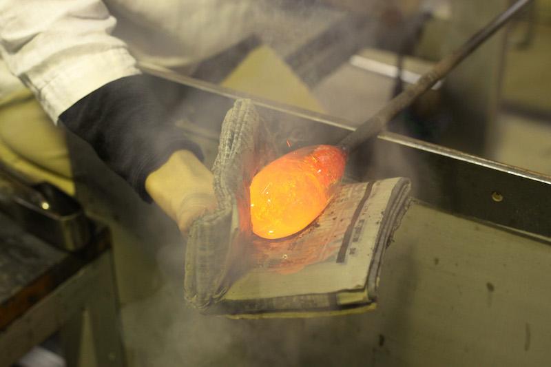 金箔を混ぜたガラスにもう一度溶解炉のガラスを巻き、手のひらより少し大きめに畳んで水に濡らした新聞紙でガラスの形を整える。すごい迫力でドキドキした瞬間
