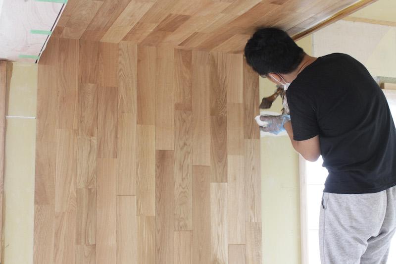 天井に貼られたフローリング材の横の部分をオイル塗装で着色している(撮影:おおかわらあさこ)