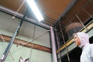 小森さんの頭上にあるタンクには、お店こだわりの醤油が入っている。仕入れた醤油は写真左の管からタンクへと運ばれる。機能的な配管に目をうばわれる