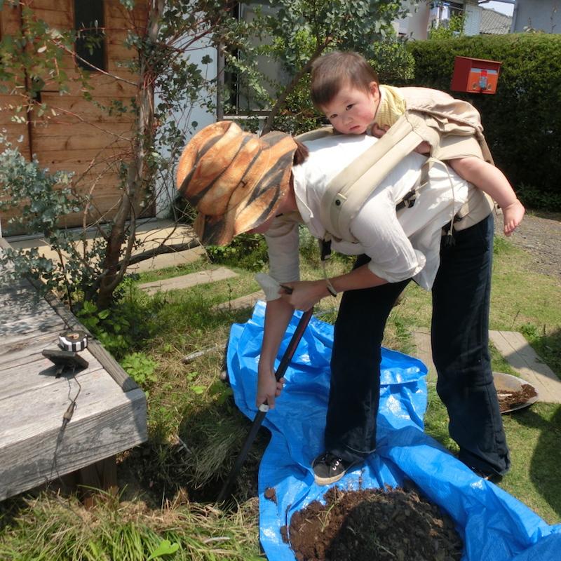 赤ちゃんを背負いながらバールで土をほぐす