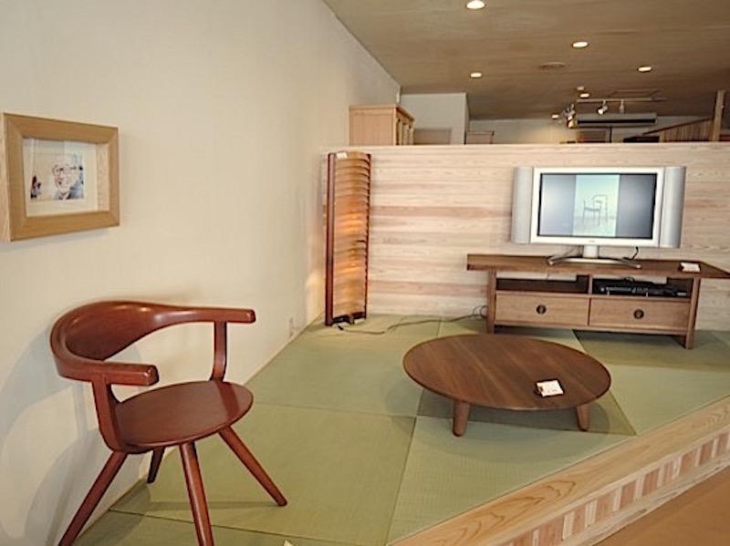 木村さんが敬愛する菅沼謙司前社長が笑顔で見守る「座」のコーナー。御膳風の一人卓は菅沼さんのデザイン。「人は上半身が見えると安心すると言っていた。畳をこよなく愛した人でした」