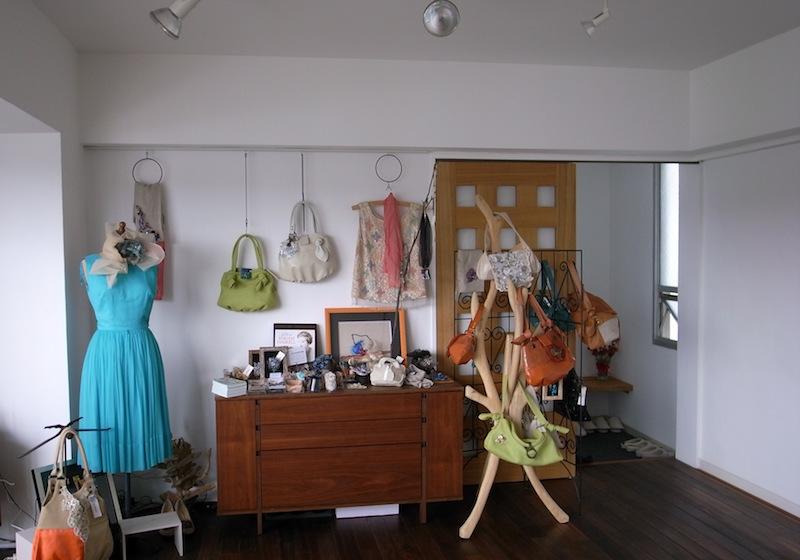 玄関側の壁一面に作品が展示されている。バッグやドレス、ストール、アクセサリーなど、幅広い作品群