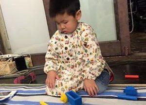 さっそくママ手作りのスモックに袖を通す男の子。「下の子が生まれ、家で落ち着いて作業することができない。子どもをみてくれているこの環境があったから作ることができた」とママ。直線縫いでできる袋物と違い、スモックは特に技術と時間がかかるグッズの一つだった12 写真キャプション(ずらりせいぞろい)