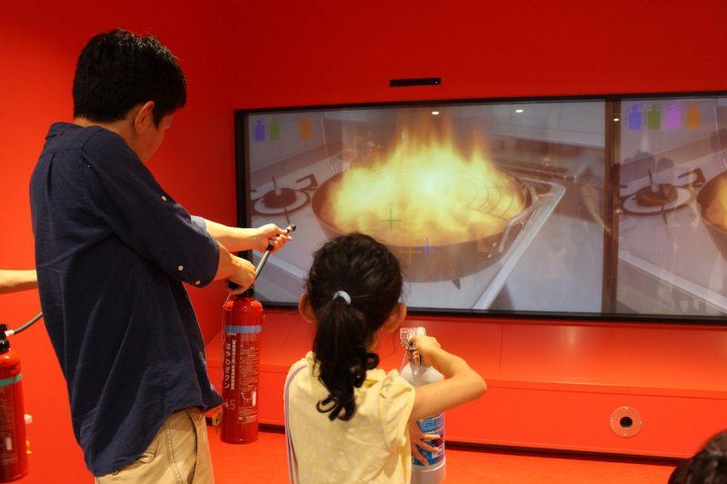 火災シミュレーターでは実際に消火活動を体験できる。小学生の長女も参加。案内スタッフの方によると「火災時は、小学生が消火することは難しいです。まずは火事だ! と叫んで119番通報し、子どもを逃げさせて大人が初期消火するように」