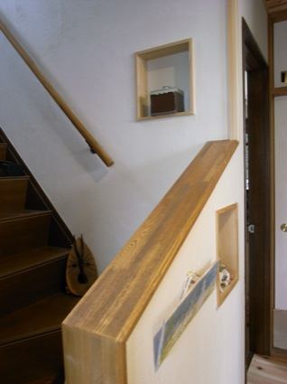 玄関と階段回りは白い土壁で統一。階段の壁にニッチを設け、そこに作品を飾れるようにしている