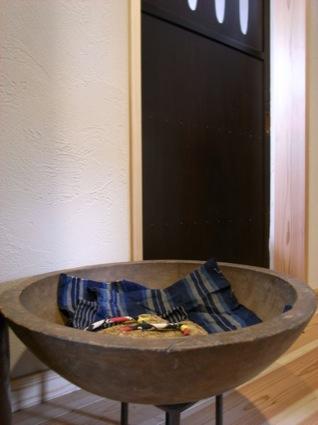 洗面所の建具はアンティーク。片山さんが選んできたものに合わせて戸の框を設計できるのも、オーダーメイドのリフォームならでは。やはり骨董のこね鉢をスリッパ置きにして、玄関回り全体の統一感が出た