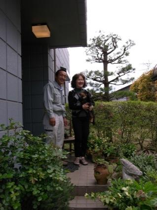 玄関前で、ウィズの森の玉置さんと愛犬・ショコラと一緒に。庭のグリーンの鉢なども、焼き物が多い。今後は庭も含め、「屋外とリビングがつなげる形でリフォームしたい」と話がはずんだ
