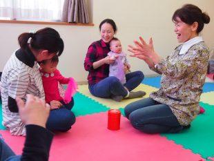 参加する親子と心を通わせながら進めるわらべうたの教室。菅野さん(右)は赤ちゃん一人ひとりに励ましの声をかける