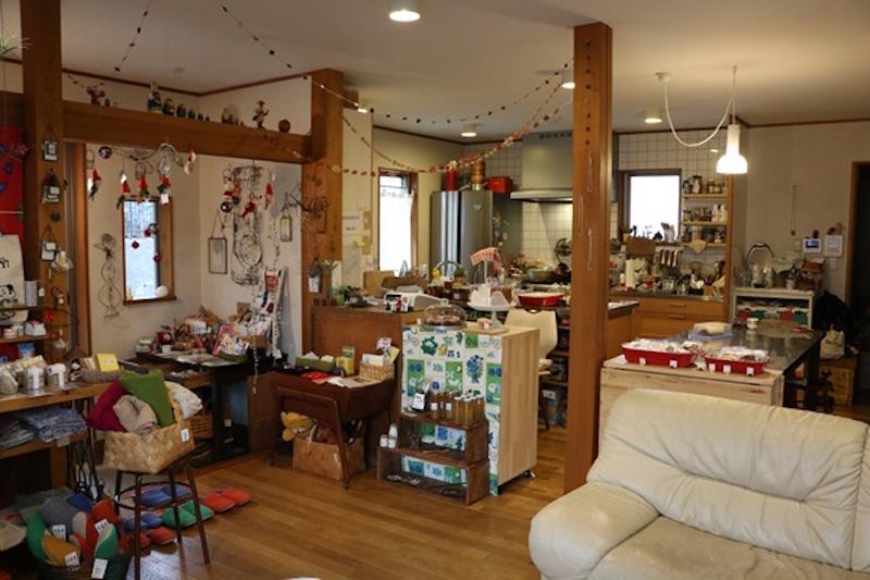 作業台のある大きなキッチン、ダイニングテーブル、ソファーのある空間は自宅カフェならではの居心地の良さ。ワイヤーオブジェやお子さんの絵などもインテリアの一部。なんともいえぬ温かい空気が流れでいる
